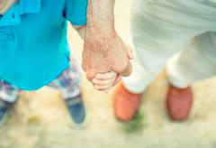 Child holding hand of senior man in the nature Stock Photos