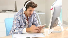 Student in office working on tablet with headphones on Stock Footage