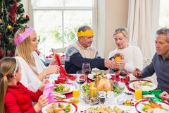 Family in party hat having fun at christmas time - stock photo
