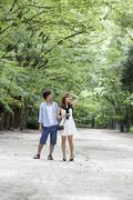 a couple, a man and woman in a kyoto park in an avenue of mature trees. - stock photo