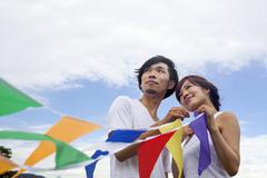 A couple, a man and woman in a kyoto park holding up a colourful row of flags Stock Photos