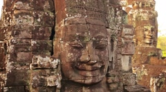 Giant, ancient, sculpted stone faces at bayon temple, cambodia Stock Footage