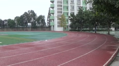 Empty athletic track and football playground after rain in a high school Stock Footage