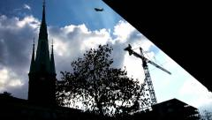 A silhouette church, tree, constructing building, birds, airplane flying in sky Stock Footage