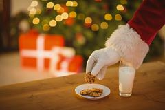 Stock Photo of Hand of santa claus picking cookie