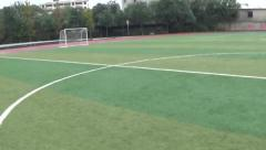 Running on an empty soccer field in a high school, POV shot Stock Footage