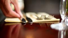 Extreme Close-Up of Someone Laying Out Knives and Forks on a Wooden Dining Ta - stock footage