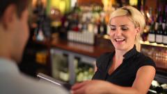 Man Purchasing Items From an Employee at a Bar Stock Footage