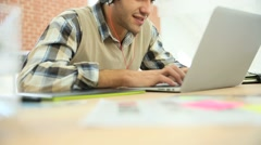Young office worker using headphones in front of laptop Stock Footage