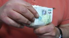 Sterling notes (British pounds) being checked and folded - stock footage