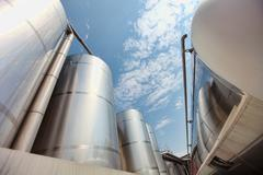 Silver silos and tank - industrial infrastructure in wide lens Stock Photos