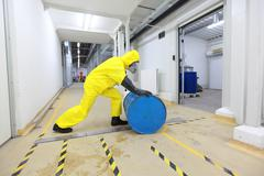 Worker in protective coveralls working barrel with toxic substance Stock Photos