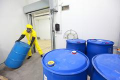 worker in protective coveralls working barrel with toxic substance - stock photo