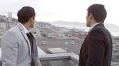 Two men in suits stand on a roof and look out to city below them Stock Footage