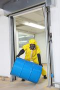 Worker in protective coveralls lifting barrel of toxic substance Stock Photos
