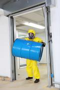 Worker in protective uniform lifting barrel of toxic substance - stock photo