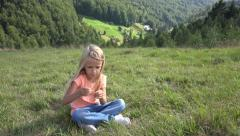 4K Thinking Girl Playing in Grass, Child Relaxing Outdoor, Mountains Countryside Stock Footage