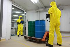 Workers in protective uniforms working with barrels of chemicals on forklift Stock Photos