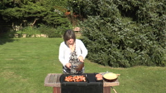 Woman preparing chicken to cook on the outdoor barbecue - stock footage