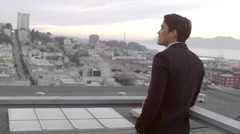 A man in a suit stands on a roof and looks down on the city and then turns Stock Footage