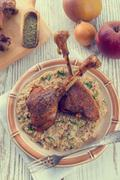 roasted goose thighs with grits - retro vintage - stock photo