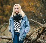 Young cute blonde woman in jeans, scarf, and sweater - stock photo