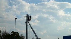 Operator repair power line outside arm lift , on aerial platform Stock Footage