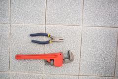 Wrench and pliers on bathroom floor - stock photo