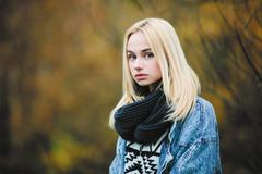 Young cute blonde woman in jeans, scarf, and sweater Stock Photos