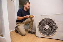 Focused handyman fixing air conditioning - stock photo
