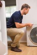 Focused handyman fixing air conditioning Stock Photos