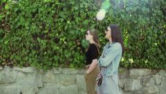Happy women walking on the street and chatting, steadycam shot Stock Footage