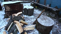 Young man is chopping wood in winter time Stock Footage