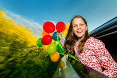Laughing long-haired young girl with colourful balloons Stock Photos