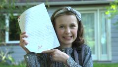 A girl shows off her A+ mark for her homework in front of her home. Stock Footage