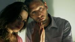 Sad couple separated by the window looking to the camera Stock Footage