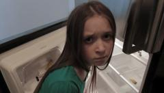 A young girl looks up from an empty fridge Stock Footage