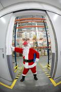 santa claus manager  at the gate to storehouse full of goods - stock photo