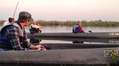 People sit in canoes in hippo infested waters in Botswana. - stock footage