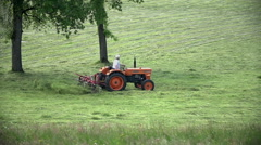 Person mixing grass with tractor in slow motion Stock Footage