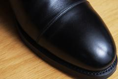 Front detail of a black leather classic shoe on a dance floor Kuvituskuvat