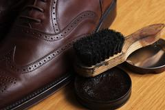 Laced brown leather classic Brogue shoes with polishing cream and brush - stock photo