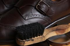 Brown leather classic Brogue shoes with polishing cream and wooden brush - stock photo