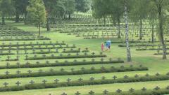 Family walking through headstones in the Lommel German war cemetery, Lommel, Bel Stock Footage