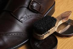 Brown leather classic Brogue shoes with polishing cream and brush on a table - stock photo