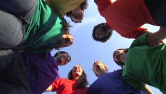 Racially-diverse group in colored t-shirts laugh and chat. Stock Footage