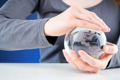 protecting the world - hands holding a globe - stock photo