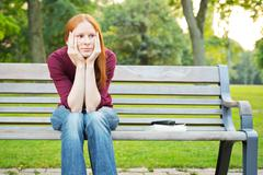 Bored woman sitting on a bench Stock Photos