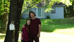 A tween girl and father wave at camera in front of their home Stock Footage