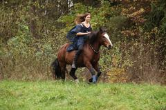 Amazing girl with horse running without bridle and saddle Stock Photos